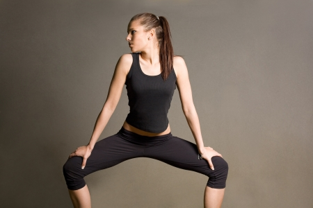 Slender fit young brunette in yoga squat pose. Stock Photo