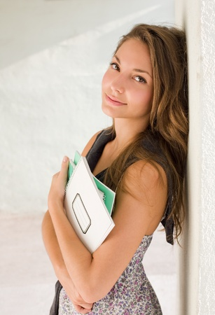 End of summer, relaxed young student girl holding exercise books. photo