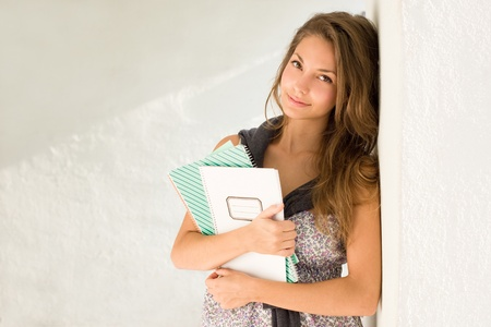 Portrait of a gorgeous young student girl holding exercise books. photo