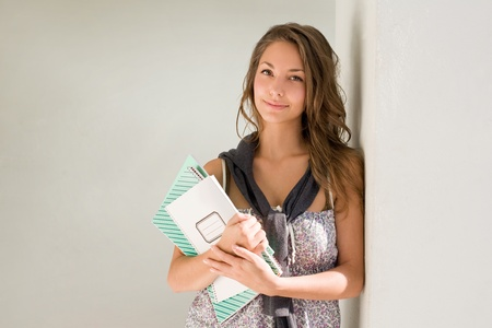 Beautiful relaxed young student girl with exercise books. Stock Photo