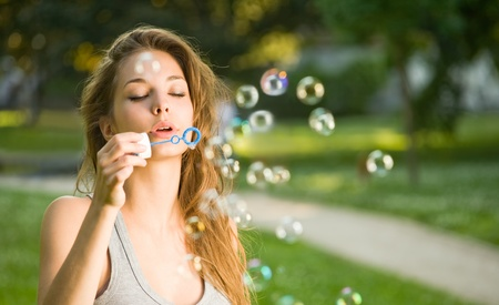 Beautiful young brunette girl blowing soap bubbles outdoors. photo