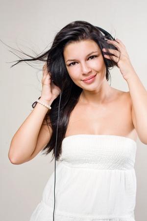 windblown: Portrait of beautiful brunette music lover with windblown hair.