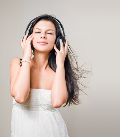Portrait of beautiful brunette music lover with windblown hair. photo