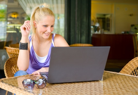 Portrait ofd beautiful young blonde woman being happy about findings through her laptop photo