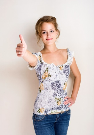 Half figure portrait of a cheerful fashionable young blond woman showing thumbs up. photo