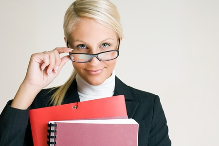 Portrait of cheerful young business woman in glasses holding folders. Stock Photo - 10771785