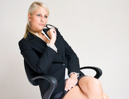 gorgeous businesswoman: Portrait of Serious young business woman sitting in office chair, pondering.