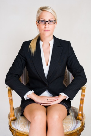 Portrait of stern looking young business woman sitting in expensive antique chair photo