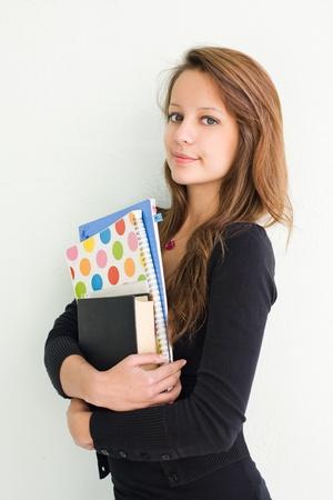 smirk: Half length portrait of beautiful teen student girl with smirk, holding exercise books.