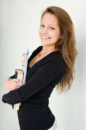 half  length: Half length portrait of attractive teen student holding exercise books.