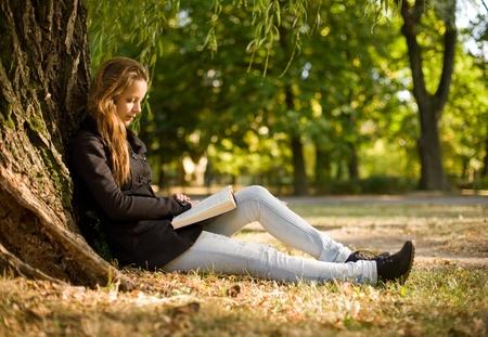 mujer leyendo libro: Retrato de la hermosa joven muchacha morena leer un libro en el parque en otoño. Foto de archivo