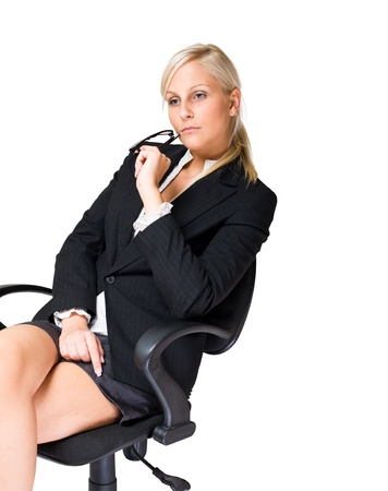 Thoughtful blond business woman sitting in office chair. photo