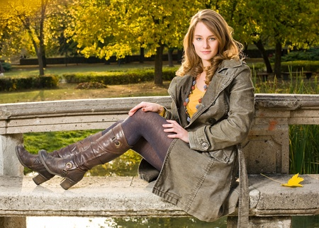 Full figure portrait of beautiful young woman in the park at fall. photo