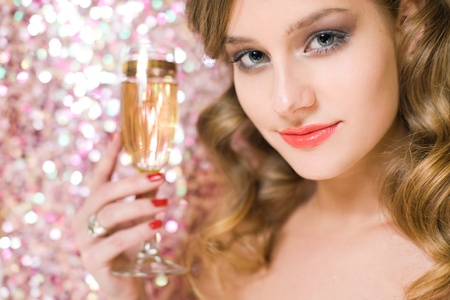 Closeup portrait of festive young blond holding glass of champagne with shiny pink background. photo