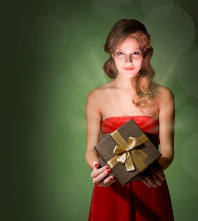 Half length portrait of beautiful blond holding gift box with creative lighting. photo