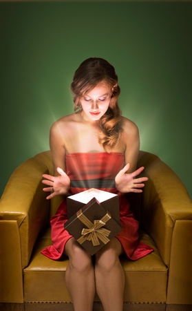 Surprised beautiful young blond with christmas gift box in creative lighting. photo