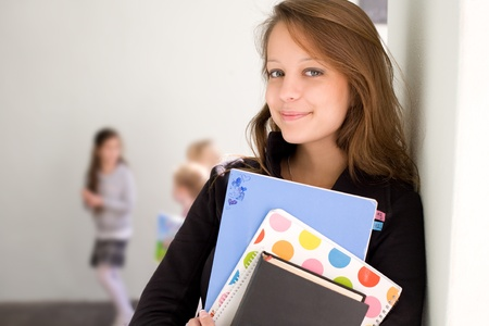 toothy smile: Half length portrait of a beautiful smiling young student with exercise books.