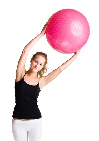 Half length portrait of fit young blond woman holding yoga ball.
