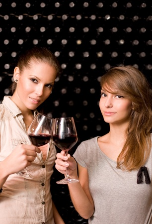 Portrait of two beautiful brunette women tasting red wine in the cellar. Stock Photo - 11266953