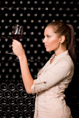 tasting: Beautiful young brunette woman tasting wine, checking the color in the wine cellar.