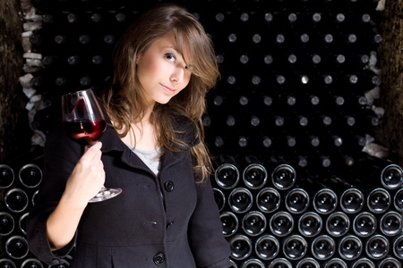 wine cellar: Portrait of a beautiful young woman tasting red wine in the wine cellar.