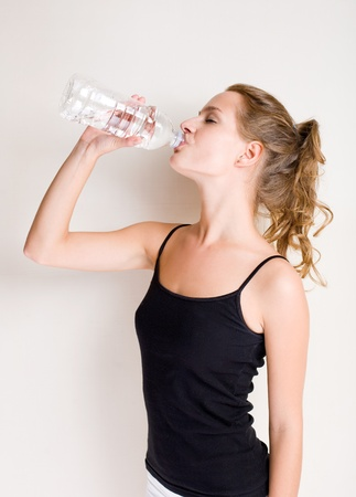 Portrait of gorgeous young woman drinking after workout. photo