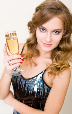 Portrait of a beautiful young blond woman with a glass of champagne. photo