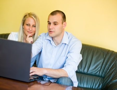 Portrait of attractive young couple using laptop at home. photo