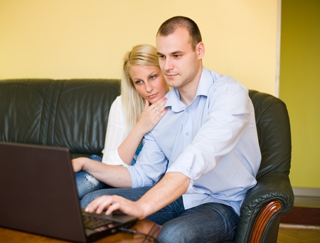 Portrait of attractive young couple shopping online using laptop at home. photo
