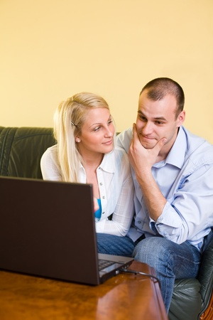 Portrait of young couple browsing the net on laptop at home. photo