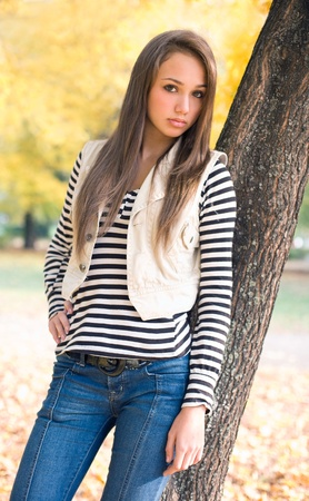 Beautiful slender young brunette model posing in the park.
