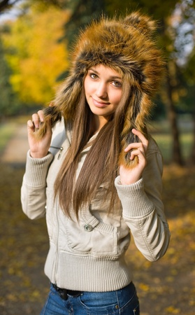 Outdoors portrait of fashionable young brunette wearing russian style fur hat. photo