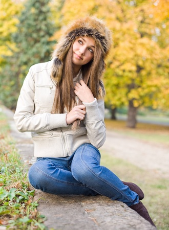 Cute beautiful young brunette girl posing outdoors in big russian style fur hat. photo