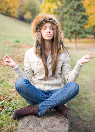 mockery: Beautiful funny young brunette model in fake meditation pose, mockery. Stock Photo
