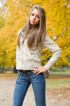 Beautiful young model dressed for chilly weather posing outdoors in the park. Stock Photo - 11423330