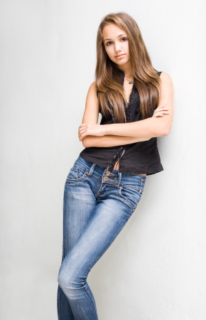 Portrait of fashionable young brunette model in blue jeans and black top.
