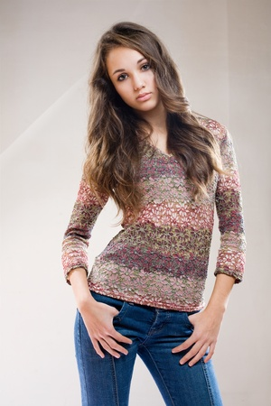 Half length portrait of beautiful fashionable brunette model in jeans and floral pattern sweater. photo