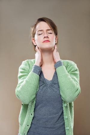 pains: Portrait of beautiful young woman stressed out by neck pains. Stock Photo