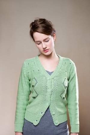 Portrait of exhausted looking young woman in green sweater. photo