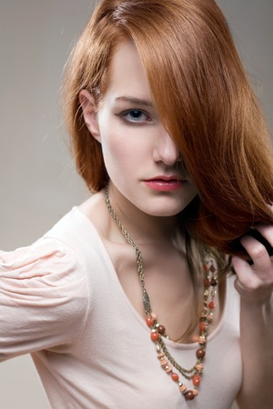 pale colours: Artistic portrait of gorgeous young redhead with intense look on her face. Stock Photo