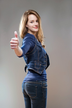 Portrait of pretty young woman in jeans and vest showing thumbs up. photo