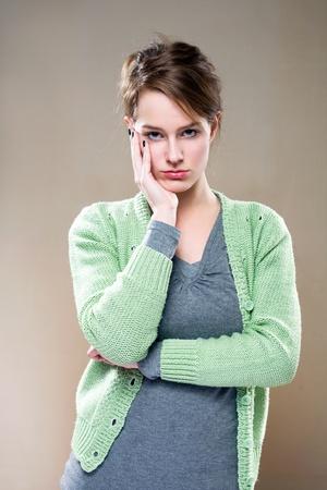 answers questions: Ritratto di bella giovane donna bruna con stanca, riflettendo espressione facciale.