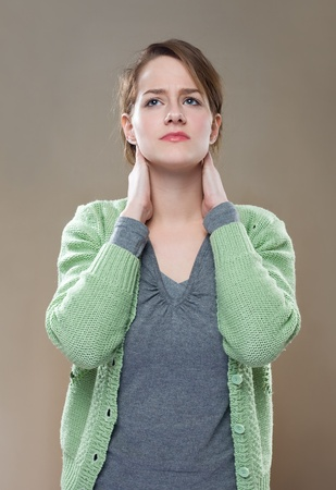 Porrait of fashionable young brunette woman showing symptoms of neck pain. Stock Photo - 11862829