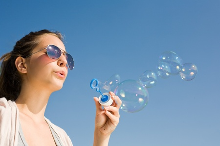 soap bubbles: Beautiful young brunette woman blowing soap bubbles into blue sky.