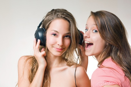 exuberant: Two beautiful young brunette teens with exuberant expression and a headhone. Stock Photo