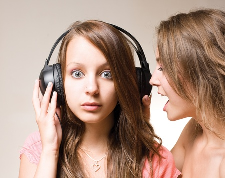 wide eyed: Two gorgeous brunette teens with a headphone. Stock Photo