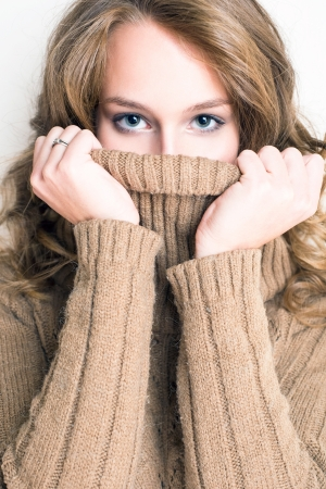 turtleneck: Fashionable young blonde woman hiding in her warm winter turtleneck sweater.