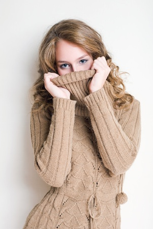 woman sweater: Beautiful young blond woman playing with her turtleneck sweater.