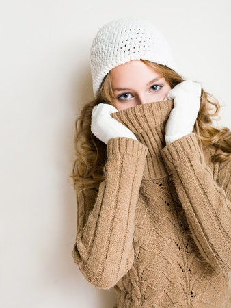 Fashionable young blonde woman hiding in her warm winter turtleneck sweater. photo