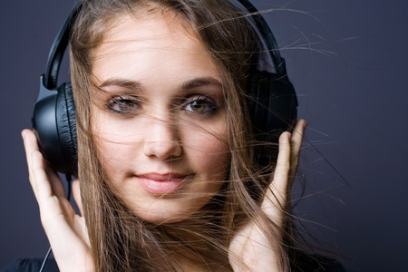Artistic portrait of a beautiful young brunette with headphones and flowing hair. photo
